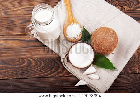 A mason jar full of sweet coconut milk, a wooden spoon with coco chips and coconuts on a wooden table background. Coconuts with leaves on a light gray sack. Coconut products.