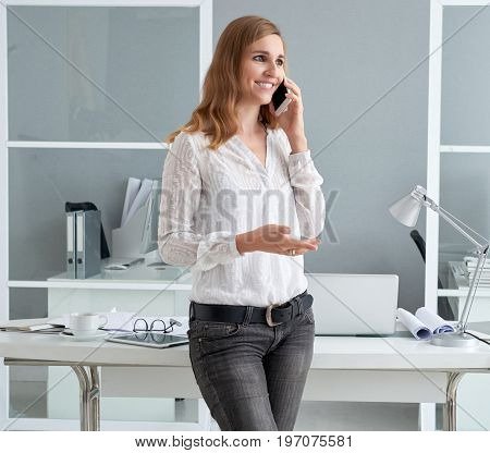 Cheerful young business lady talking on the phone