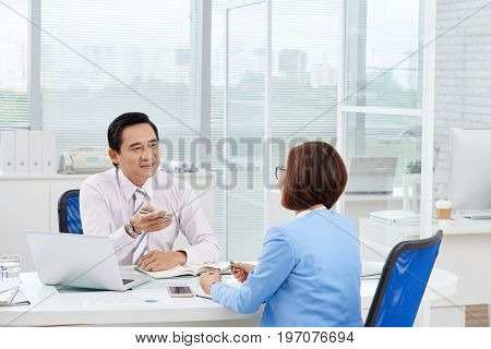 Business people discussing various issues during meeting in office