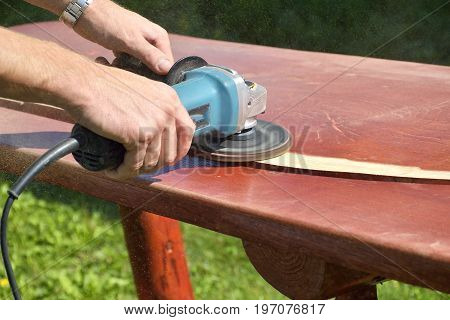 Sanding wooden table. Close-up of carpenter's hands working with electric sander - polishing old color from wooden table