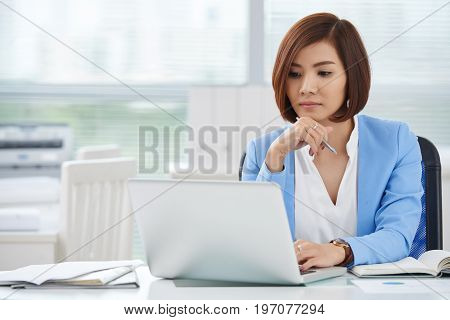Pensive young business lady reading information on laptop screen