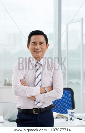 Confident middle-aged Asian businessman smiling and looking at camera