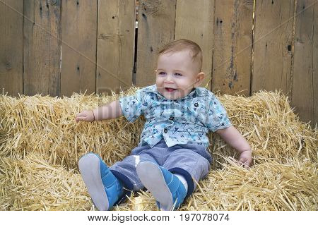 Baby Boy Is Playing On A Straw Bale.