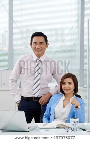 Smiling Vietnamese businessman and business lady looking at camera
