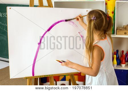 Children painting finger on easel. Group of kids girl and boy with teacher learn paint in class school. Child picture on background. Students draw a rainbow. Good psychological state of child.