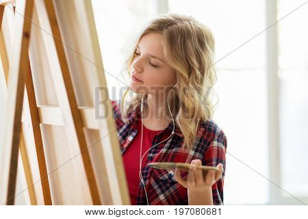 art school, creativity and people concept - student girl or artist with earphones, easel and palette painting at studio