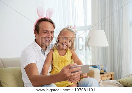 Funny father and daugher making faces and taking selfies together