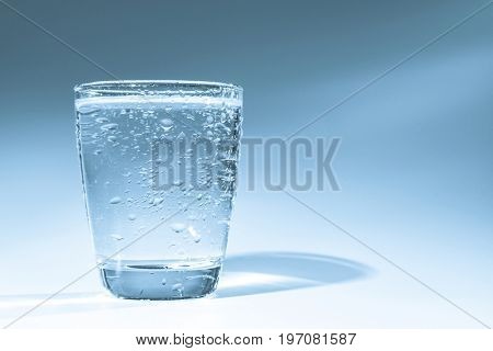 Glass with water and water drops on a blue background