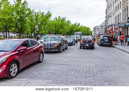 Montreal, Canada - May 27, 2017: Old Town Area With Restaurants, Cars On Road, And People Walking In