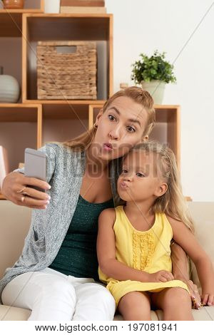 Young mother and daughter taking funny duck face selfies together at home