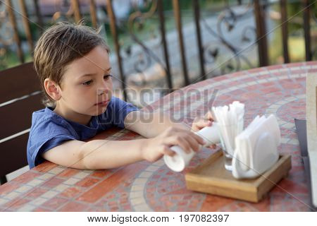 Child holding salt shaker in a cafe