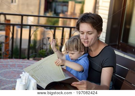 Mother With Son Holding Menu