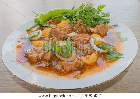 Goulash in ceramic plate. Traditional Georgian meal. Georgian goulash soup close-up on the table