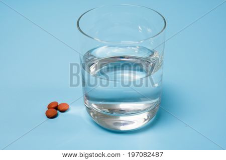 Pills and medication and a glass with water on a blue  background