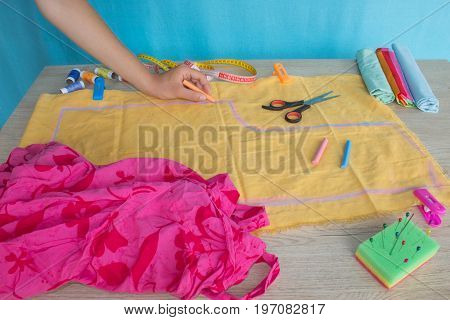 Seamstress hands on the work table with pattern and measuring tape. Tailor hands working with scissor and suit textile cloth