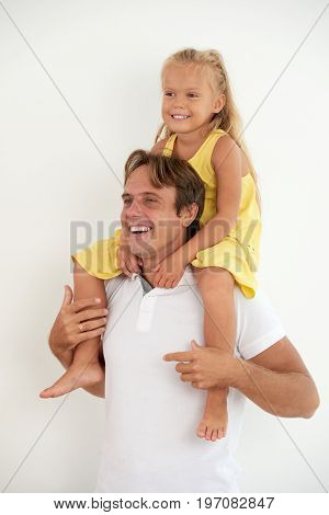 Happy father carrying her daughter on shoulders