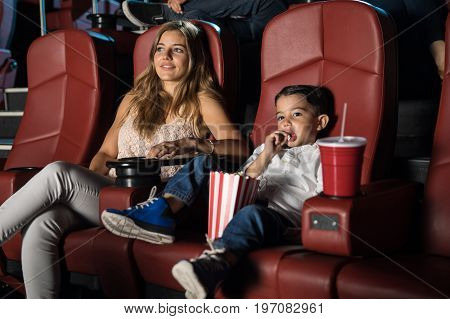 Cute boy and his mother watching a movie and eating popcorn together in a cinema theater