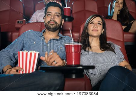Portrait of a cute Hispanic couple holding hands while watching a movie at a cinema theater