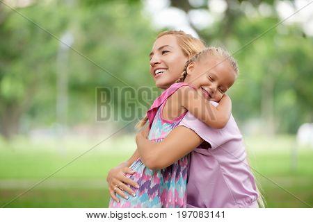 Happy adorable little girl hugging her mother