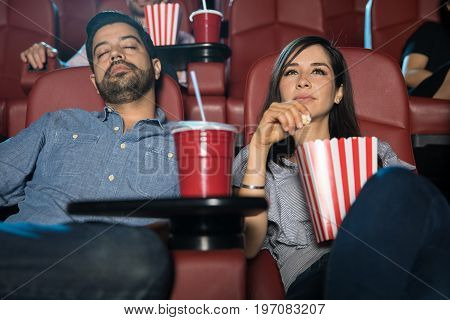 Hispanic man falling asleep next to his girlfriend while watching a movie at the cinema theater on a date