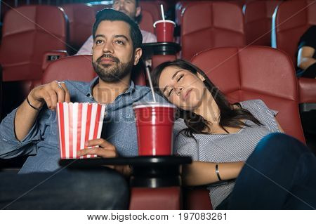 Pretty woman falling asleep next to her boyfriend at the movie theater while watching an action film