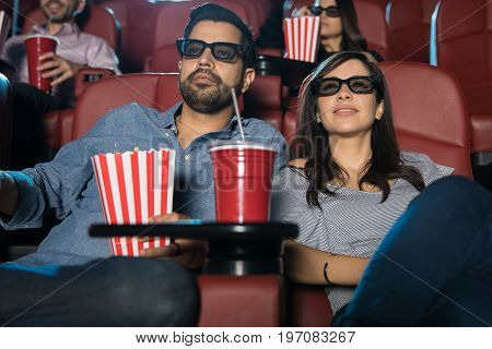Good looking Hispanic couple watching a 3d film in a movie theater