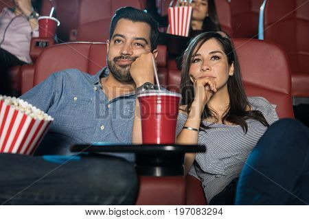 Portrait of a young couple on a date watching a really boring movie at the cinema theater