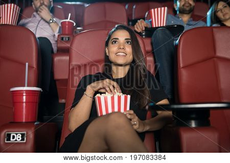 Portrait of a beautiful young Hispanic woman eating popcorn and watching a movie at the cinema theater