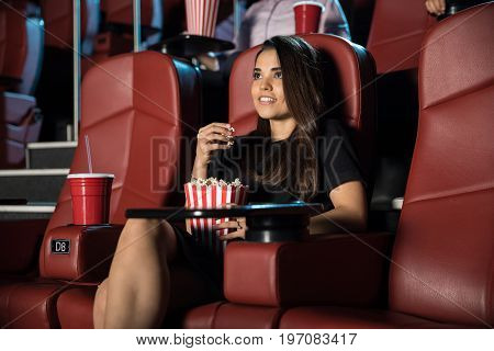 Cute young woman eating popcorn and watching a movie by herself at the cinema theater