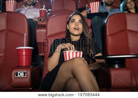 Portrait of a good looking young woman watching a scary movie and eating popcorn at the theater