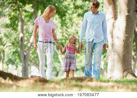 Mother and father walking with their little daughter in the park