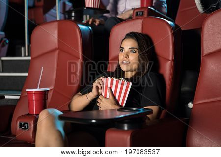 Young woman watching a really scary movie by herself at the cinema theater