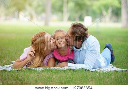 Father and mother kissing their daughter on both cheeks
