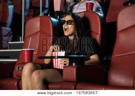 Gorgeous young Latin woman wearing 3d glasses and looking very surprised by a scene at the movie theater