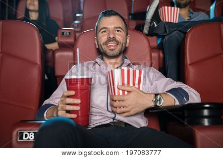 Happy young man with a beard hugging a combo of soda and popcorn while watching a movie at the cinema theater