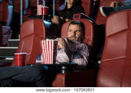 Attractive young man looking scared while watching a horror film at the movie theater