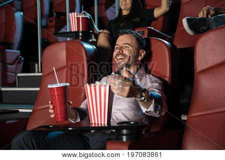 Handsome young man laughing and having a good time at the movie theater