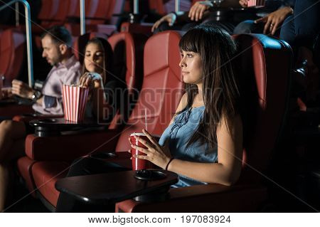 Profile view of a beautiful young brunette watching a movie by herself at the cinema theater