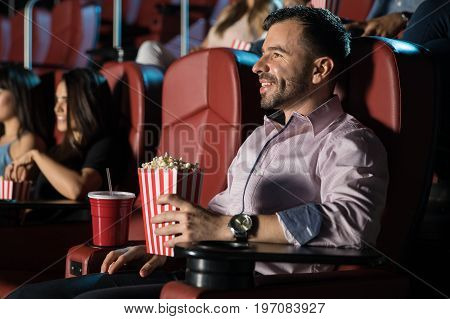 Profile view of a handsome young man eating popcorn and watching a movie by himself at the theater