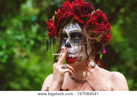 Beautiful woman smokes a cigarette in makeup traditional Mexican Calavera skull Katrina in the autumn forest in a wreath of red flowers. Day of the dead Halloween celebration.