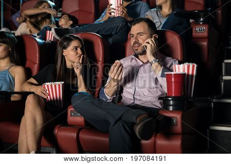 Annoying man talking on the phone at the movie theater while a woman next to him tries shushing him