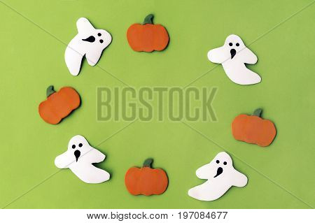 Handmade Pumpkins a ghost boo in a circle on a green paper background