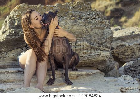 Beautiful young girl kissing her dog breed xoloitzcuintle summer on a stony beach at sunset