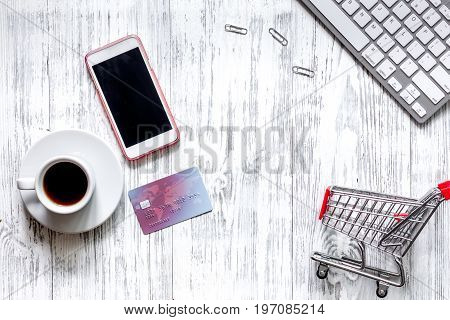 Mobile shopping. Shopping cart, phone, bank card on light wooden background top view copyspace.