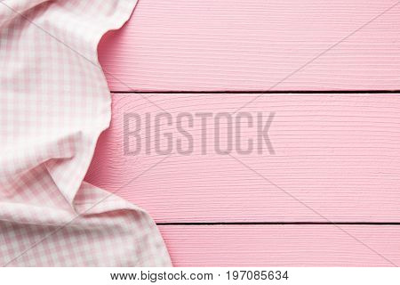 Checkered tablecloth over pink wooden table. Top view.