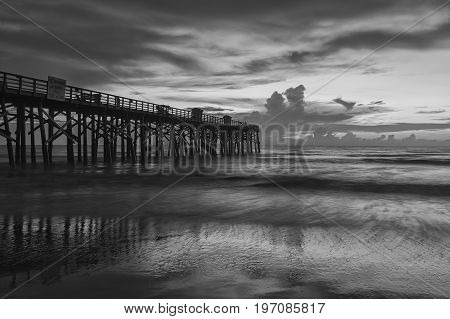 A B&W image of sunrise over the Atlantic Ocean at the pier in Flagler Beach Florida.