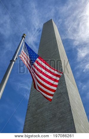 US flag and Washington Monument. A perspective of the US flag in front of the Washington monument in DC.