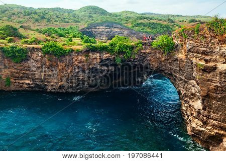 Family lifestyle. Father, mother with children walk and look at natural sea pool Broken Bay. Bali travel destination. Nusa Penida island day tour popular place. Activity on beach holiday with kids.