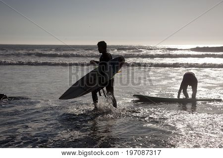 CONCON, CHILE- JULY 6 2015: Surfer walks along the beach after a fun time in the water. Image is backlit and features the subject in silhouette in Concon beach, Chile on  July 6, 2015