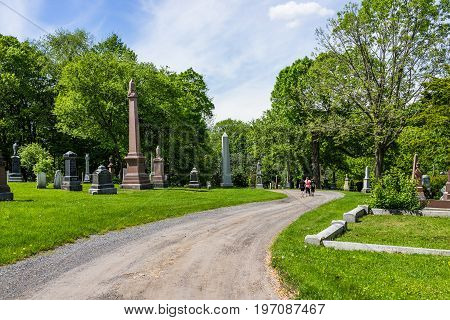 Montreal Canada - May 28 2017: Cemetery on Mont Royal with grave tombstones and people walking on trail path during bright sunny day in Quebec region city